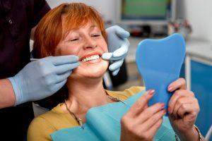 An older woman examining her teeth.