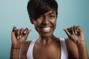 young woman smiling flossing her teeth