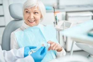 older woman learning about dental implants in Temple